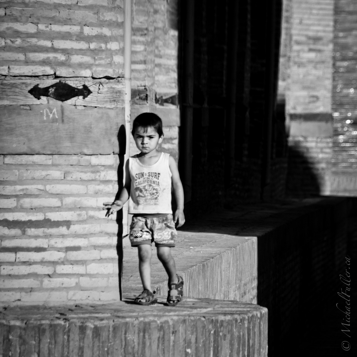 In the empty early morning streets, a child strolls aimlessly and unsupervised.