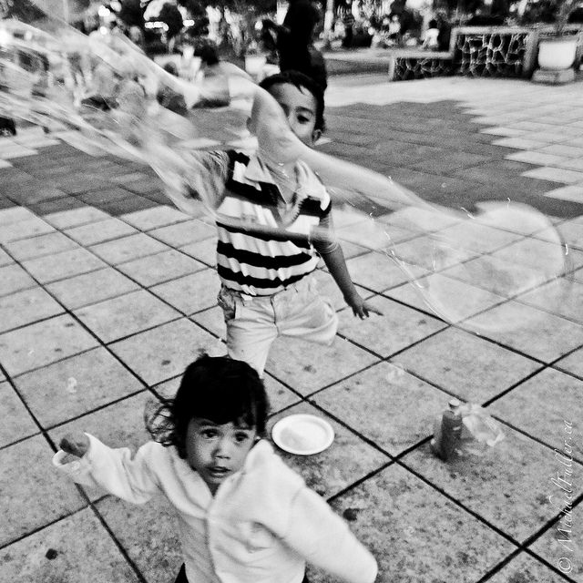 girl and brother playing with bubbles